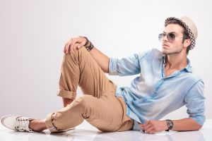 cool fashion man lying on the floor, holding one knee up, looking up