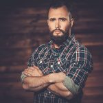 Handsome man wearing checkered shirt in wooden rural house inte